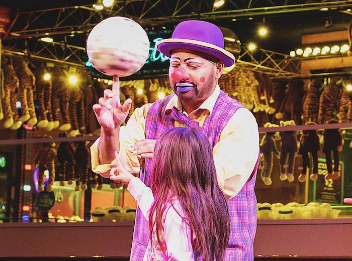 A clown helps a child spin a ball in Vegas Circus Circus